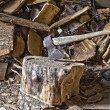 Stock Photo: Stack firewood and ax on a chopping block.
