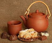 Clay teapot with sweets — Stock Photo