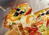 Nemen plak van pizza, gesmolten kaas druipende — Stockfoto