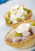 Tartlet with salad on a white plate — Stock Photo