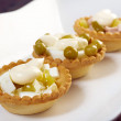 Tartlet with salad on a white plate - Stockfoto