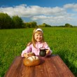Little girl drinking milk on a wooden table — Foto Stock