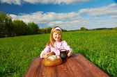 Little girl drinking milk on a wooden table — Stock Photo
