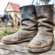 Stock Photo: Old muddy farmers boots