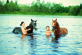 Girl bathe horse in a river — Stock Photo