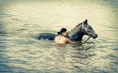 Woman swimming winth her black stallion — Stockfoto
