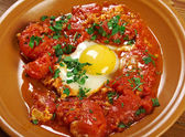 Shakshuka -dish of eggs poached in a sauce of tomatoes, chili peppers, and onions, often spiced with cumin.Moroccan, Tunisian, Libyan, Algerian, and Egyptian cuisines traditionally — Stock Photo