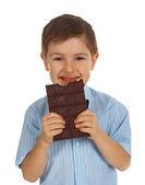 Smiling kid eating chocolate — Stock Photo