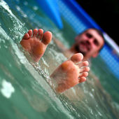 View of bare male feet at swimming pool — Stock Photo
