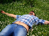 Уoung man lying in grass with flowers — Stock Photo