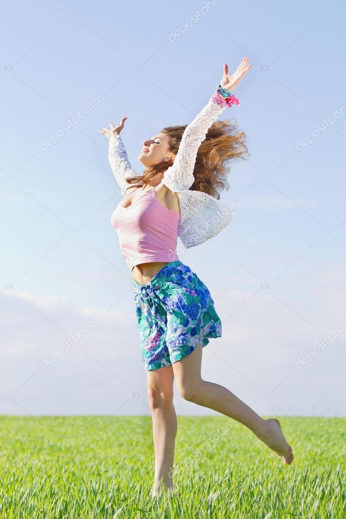 Happy beautiful young woman in a green field — Stock Photo #13441869