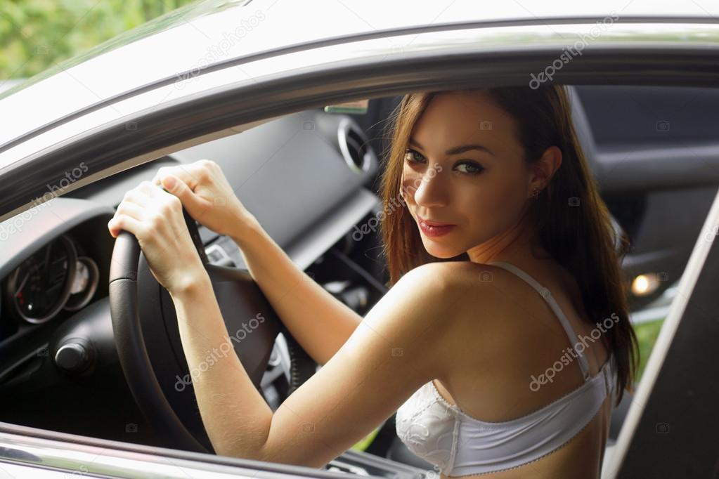 Young woman in lingerie behind the wheel of a car — Stock Photo #13441958