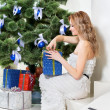 Woman opens a Christmas present — Stock Photo