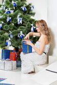 Woman opens a Christmas present — Stockfoto