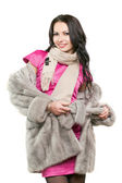 Smiling young brunette in a fur coat — Stock Photo