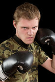 Angry young man in boxing gloves — Stock Photo