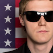 Man in sunglasses on a background of the American flag. Closeup — Stock Photo