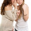 Two young gossipy women - Stock Photo