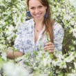 Smiling blonde in blooming garden — Stock Photo
