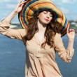 Young brunette in colorful hat — Stock Photo