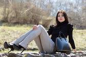 Brunette sitting on the rock — Stock Photo