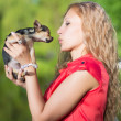 Curly blond woman kissing little dog — Foto de Stock   #49259895