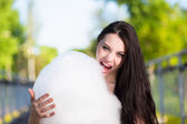 Young brunette eating cotton candy — Stock Photo