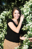 Young brunette in the flowering bushes — Stock Photo