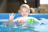 Little blond girl swimming in water pool — Stock Photo