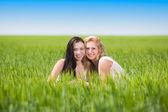 Two women in the green field — Stock Photo