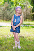 Little blond girl in jeans dress — Stok fotoğraf