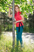 Blond woman posing near the tree — Stock Photo