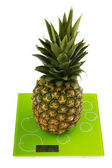 Pineapple on square kitchen scales — 图库照片