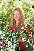 Blond woman posing near flowering bush — Stock Photo