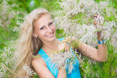 Woman posing in flowering conifer — Stock Photo