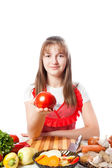 Girl the cook offers a tomato — Stock Photo