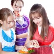 Three girls of the cook prepare a vegetarian dish — Stock Photo