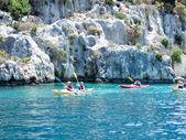 Canoeists floating near rocks — Stock Photo
