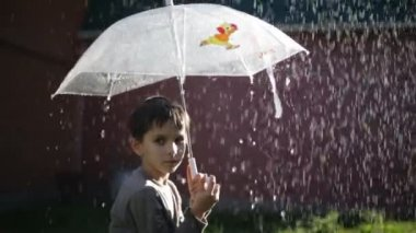 Little boyholding an umbrella in the rain — Stock Video
