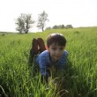 Stock Video: Boy lies in grass. Summer.