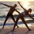 An attractive young woman and man doing yoga on a jetty with the ocean — Stock Video