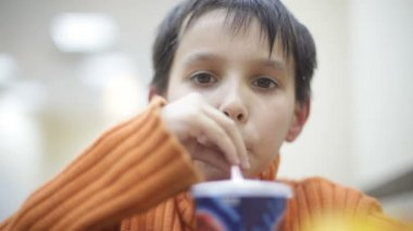 Boy drinking a soda or shake from straw — Стоковое видео