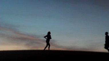 Entspannte junge heißblütige paar genießen die sonnenuntergang schönheit auf ihrer hochzeitsreise in einer wüste mit orangefarbenen hintergrund — Stockvideo