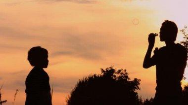 Boys blowing bubbles in a field — Stock Video