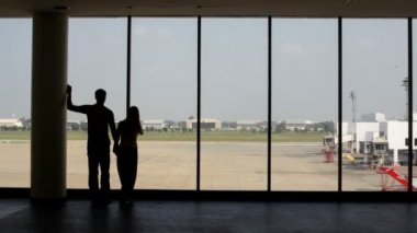 Silhouette of pair of lovers near the window in airport — Stock Video