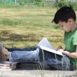 Stock Video: Boy reads book. Summer