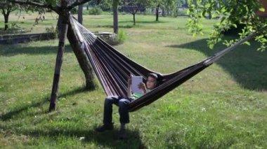 阅读和听音乐在吊床上的男孩 — 图库视频影像