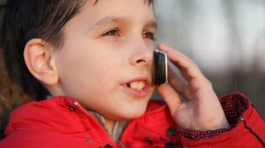 Boy talking on mobile phone outdoors — Stock Video