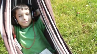 Boy reading and listening to music in hammock — Stockvideo
