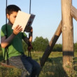 Boy reads book outdoors — Stock Video #25445753